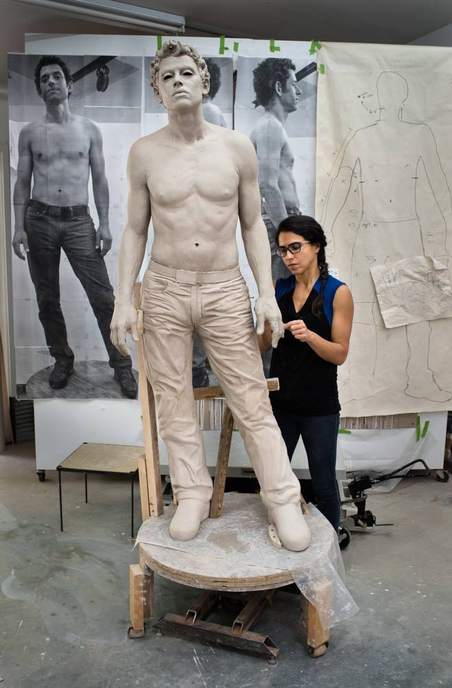 Artist working on a larger than life sculpture of a man