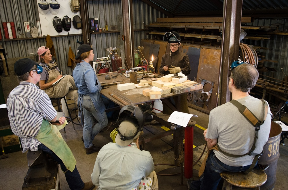Six people standing around a table of materials ready to work on metalwork